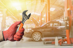 hand holding a wrench on the background of the car in the workshop